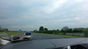 driving on the left at highway with trees and green fields