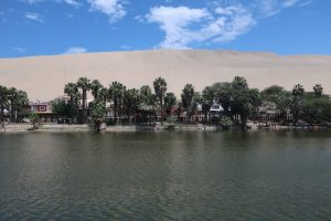 shoreside town at an oasis lake with a sand dune in the background at Huacachina, Peru