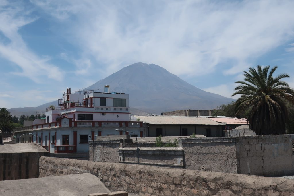 El Misti volcano towering above the streets of Arequipa city with a clouded sky above