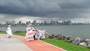 Panamanian women in traditional dress pose for a picture at Calzada de Amador, with a storm forming over Panama City across the bay